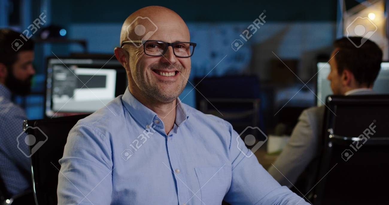 Portrait shot of bald handsome man in glasses looking seriously into the camera and than smiling. - 92664058