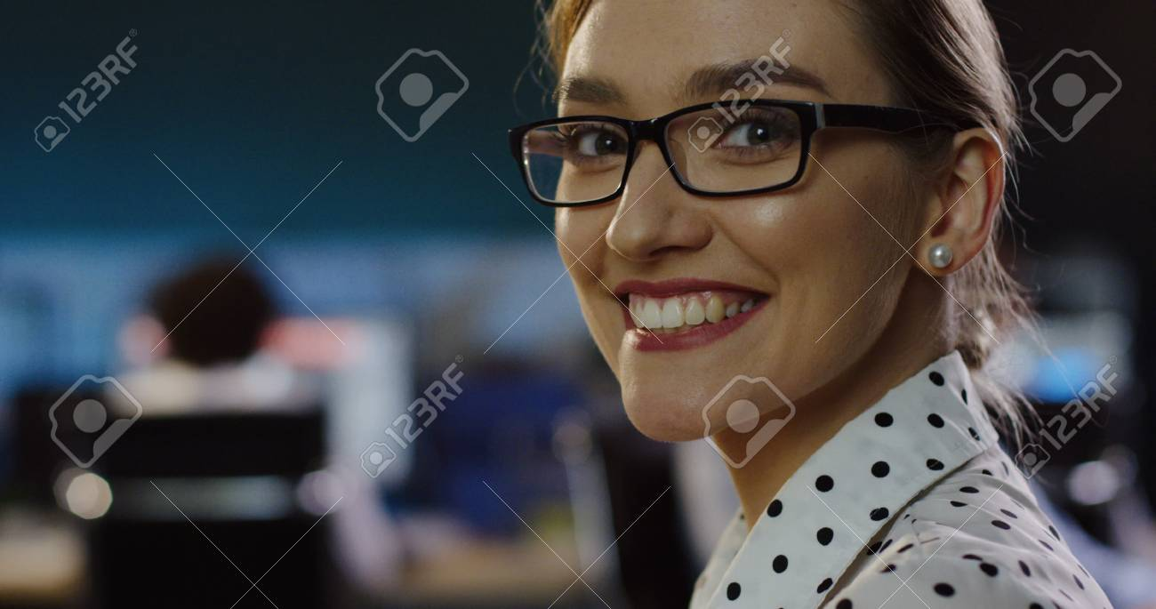 Close up of beautiful woman in glasses looking at office space behind her, than turning the head to the camera and smiling sincerely. - 92664147