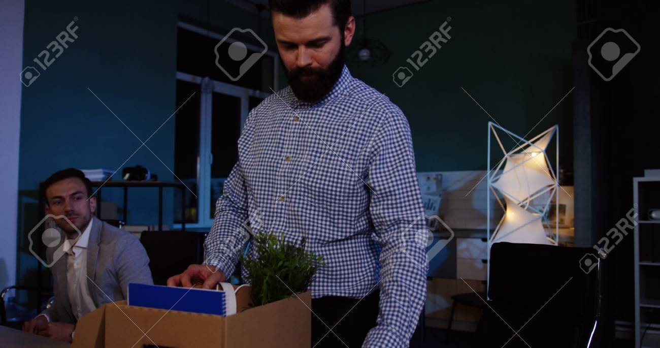 Close up of young caucasian man with a beard packing his stuff inside the box in the office at late evening because he lost his job. - 92664153