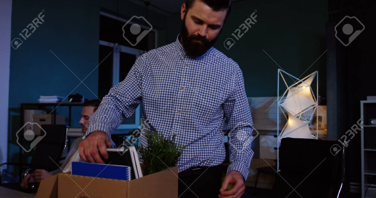 Close up of young caucasian man with a beard packing his stuff inside the box in the office at late evening because he lost his job. - 92664154