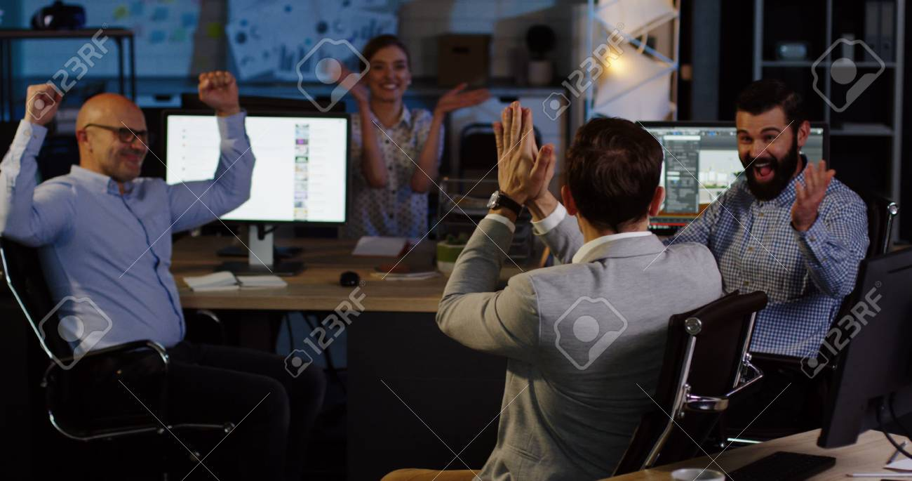 Young attractive male office worker sitting at the computer, than turning to his colleagues on the background and they celebrating his business success. - 92664180
