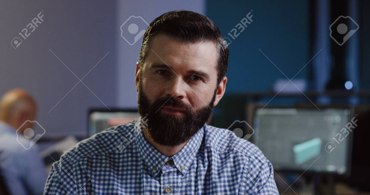 Close up of attractive man with a beard smiling into the camera sincerely on his workplace in the office. - 92664188