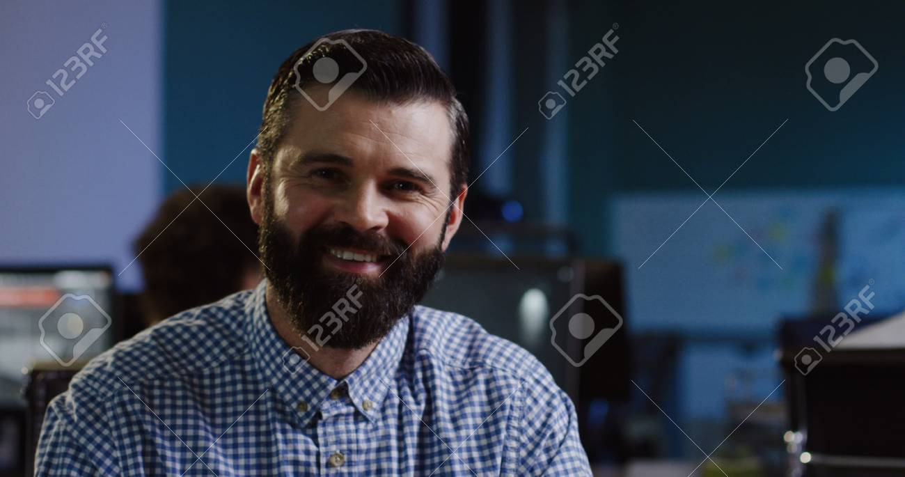 Close up of attractive man with a beard smiling into the camera sincerely on his workplace in the office. - 92664198