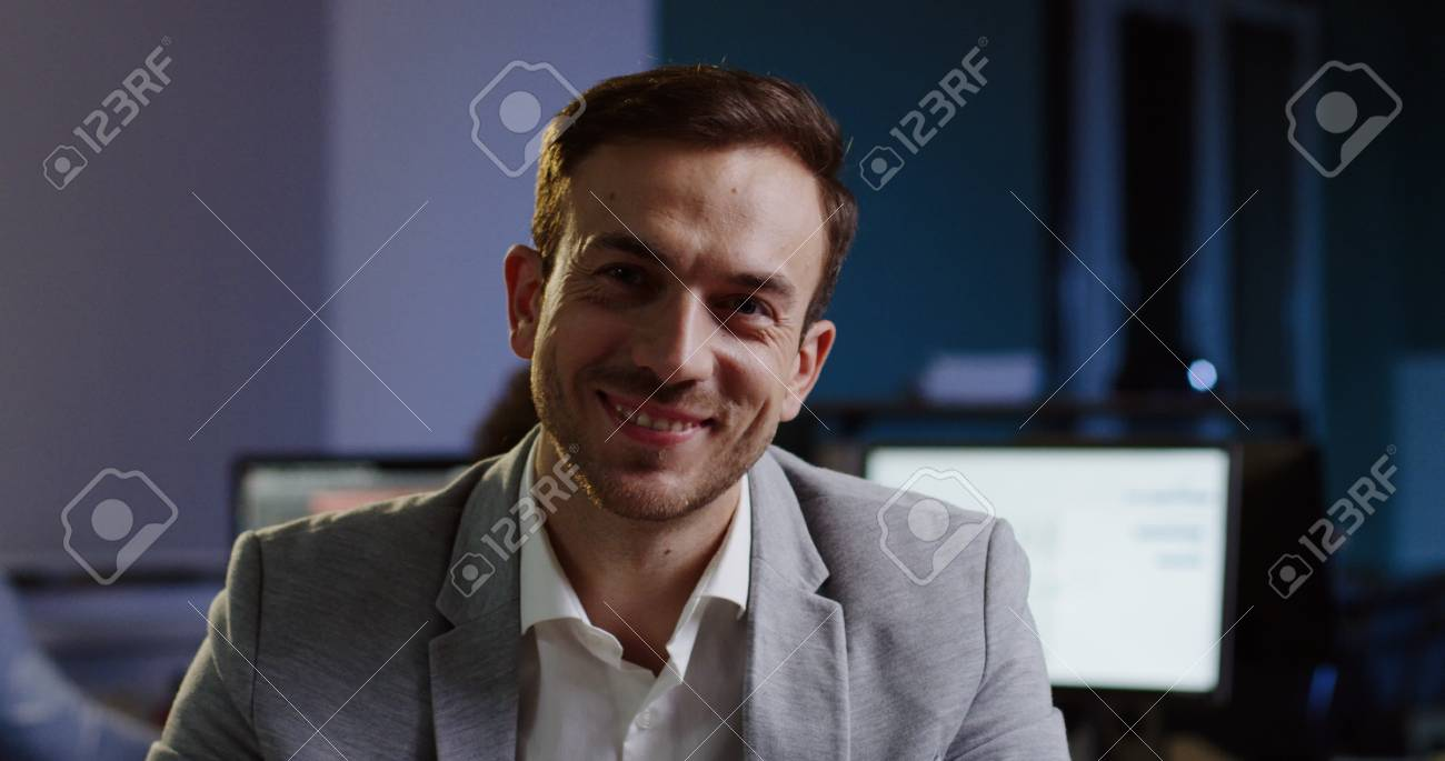 Portrait of handsome caucasian man in glasses smiling sincerely into the camera and taking off glasses on his workplace in the office. - 92664210
