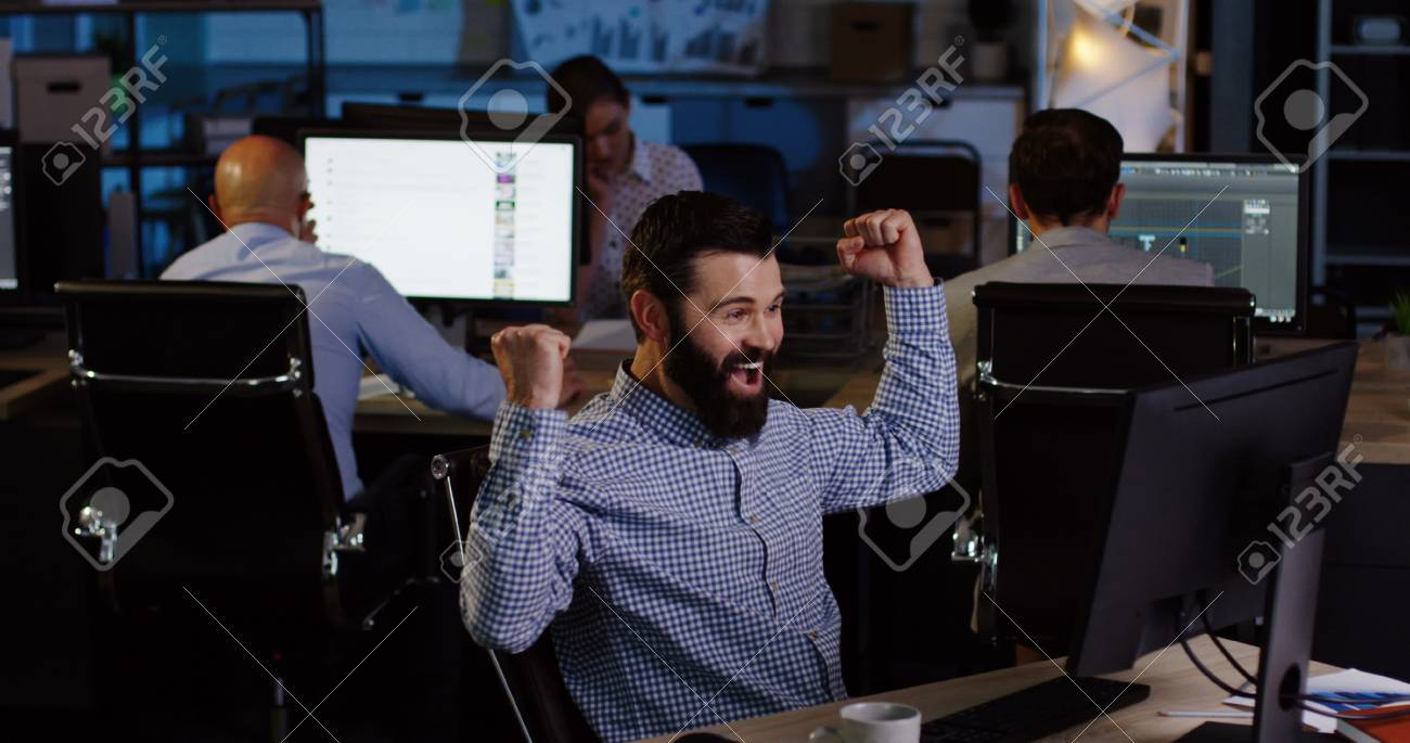 Businessmen and office workers gets excited by job done well on the computer and punches the air in late night. - 92664476