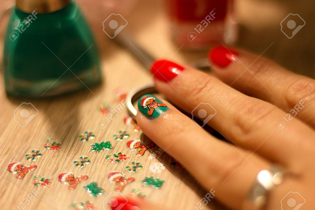 hands of a young woman who paints her nails red and green nail..