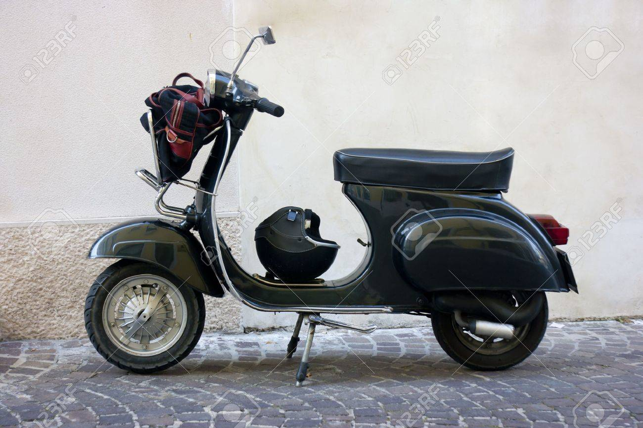 Seitenansicht von einem schwarzen Oldtimer Roller in einer kleinen Stadt in Italien Gasse Standard-Bild - 14321636