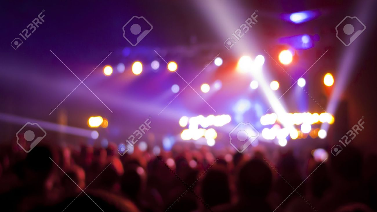 Concert audience, out of focus with stage lights and colors. Standard-Bild - 15315894