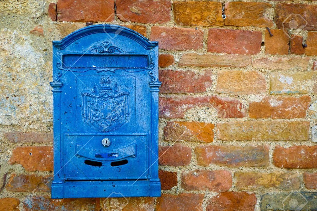 Blue metal mailbox on a brick wall in Monteriggioni, Tuscany, Italy. Standard-Bild - 17306233