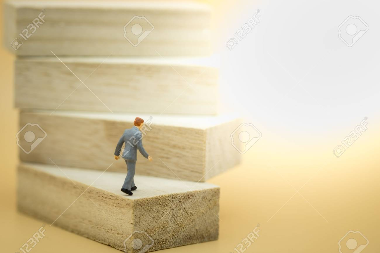 Business, growth and Succession concept. Businessman miniature figure walking to the top on wood stair made from wooden blocks toy. - 87916198