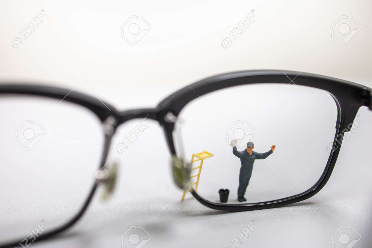 Close up of male worker miniature figure wipe and clean a dirty reading glasses with bucket and ladder. - 125696099