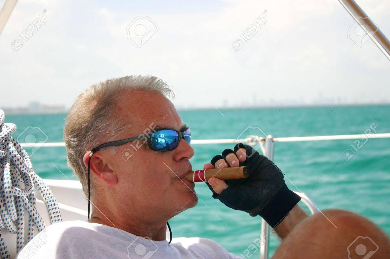 """Expresa tu momento """" in situ """" con una imagen - Página 31 11799128-hombre-de-mediana-edad-fumar-cigarros-en-velero-las-aguas-tropicales-de-la-bah%C3%ADa-de-biscayne-en-el-fon"""