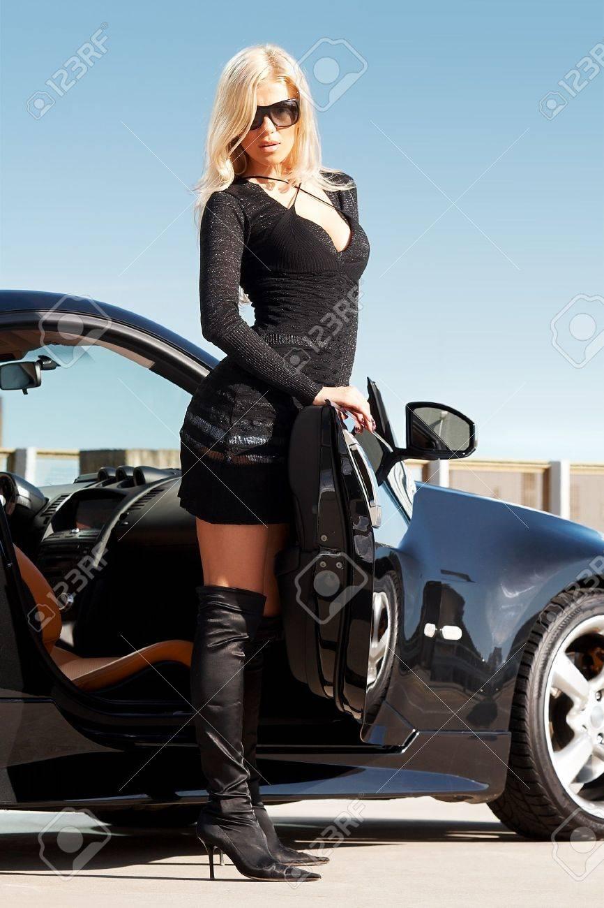 Glamorous Blond Babe Standing Near Tuned Supercar Stock Photo