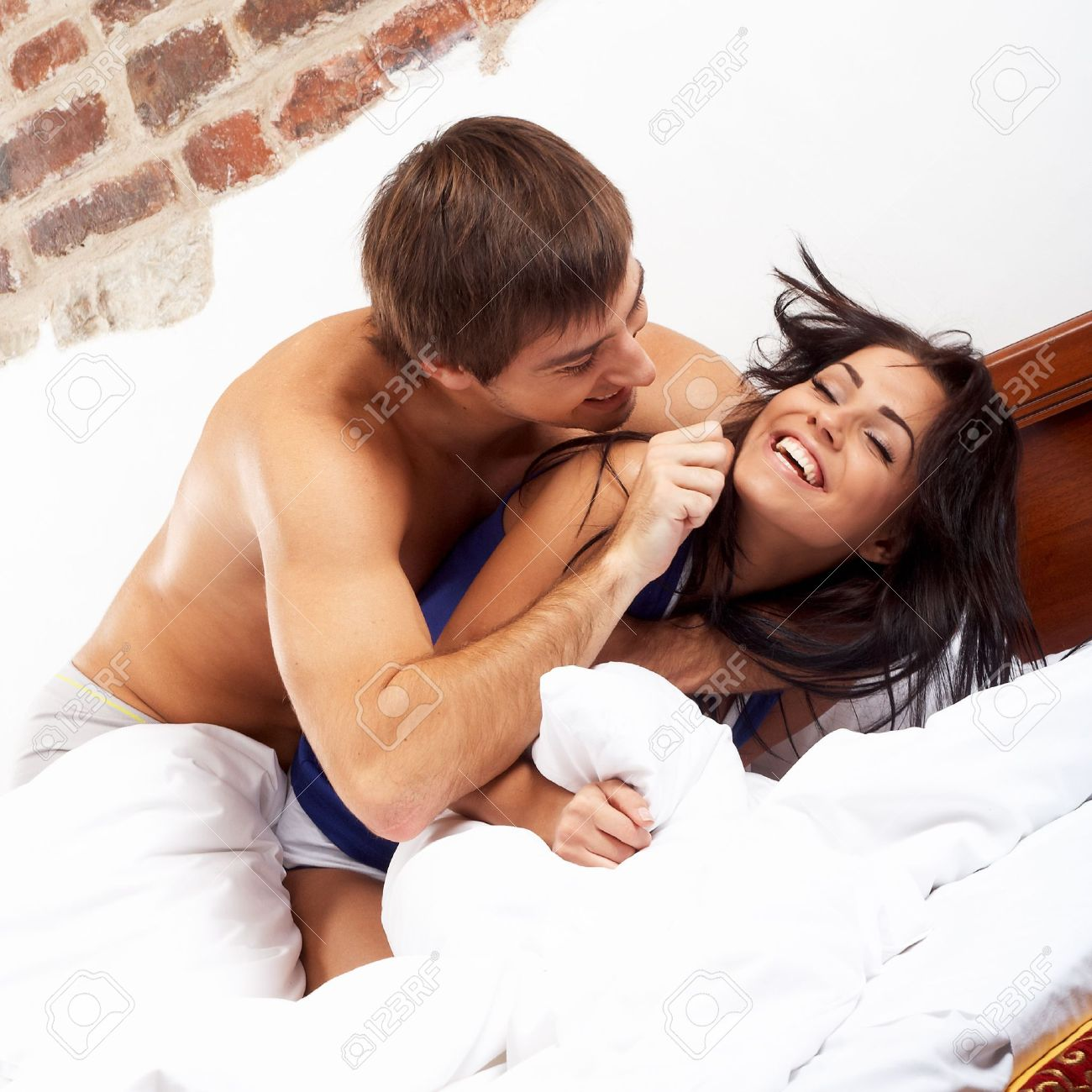 flirting couple  Young happy couple having a pillow fight in a bed. Flirting Couple Stock Photos Images  Royalty Free Flirting Couple