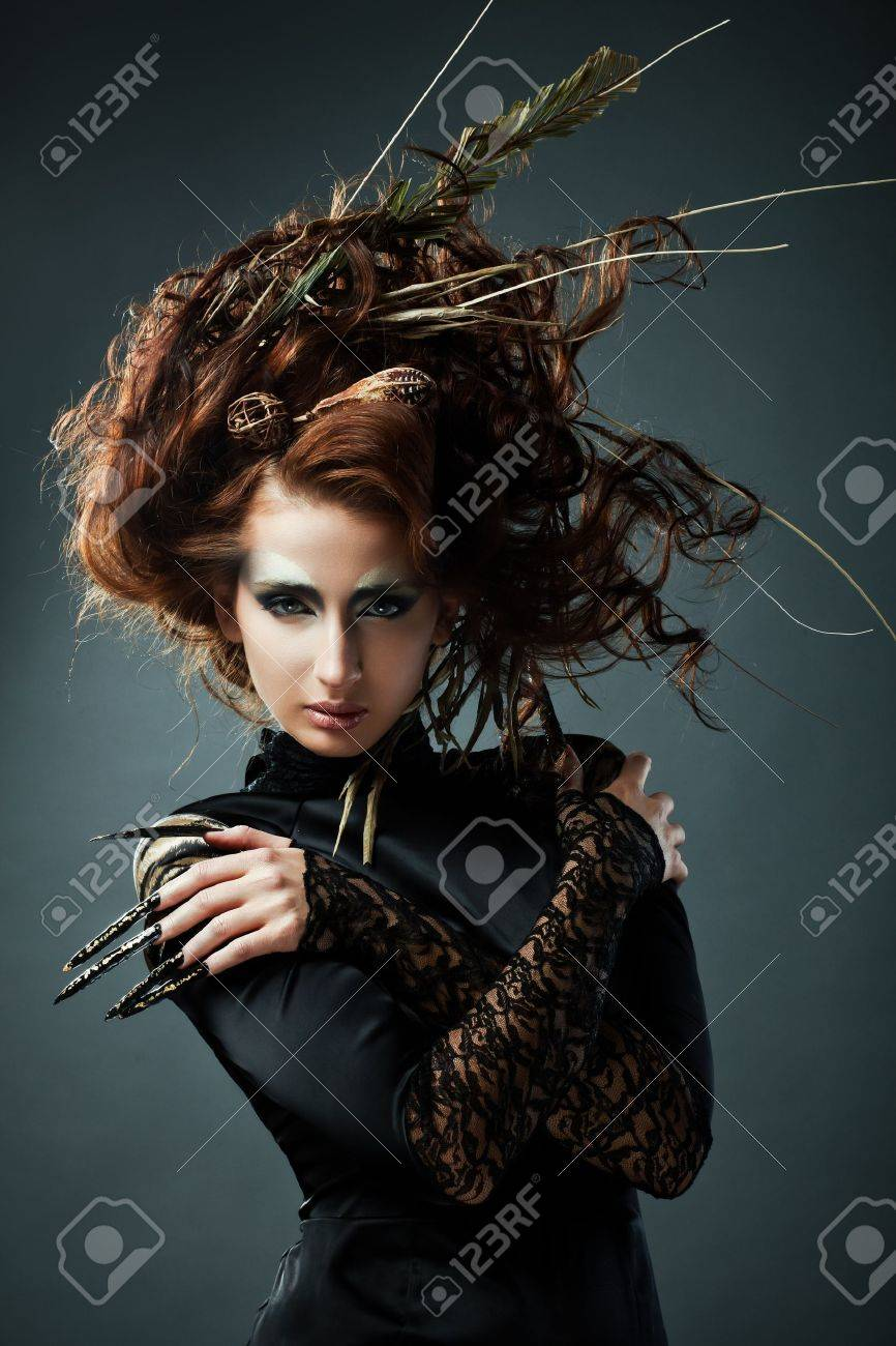 High fashion model in black dress, with long nails and creative hairstyling on grey background Stock Photo - 8388055