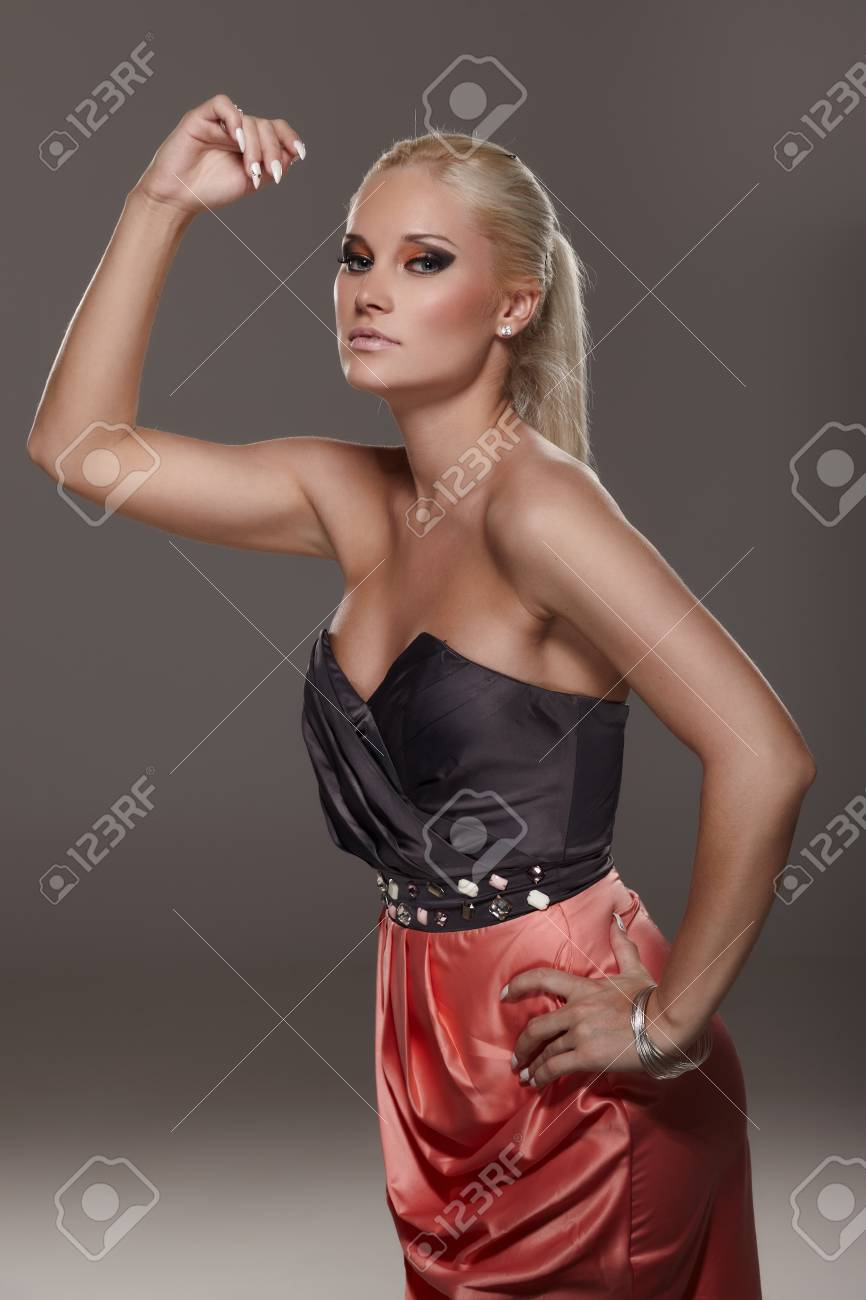 Young blond lady in a red skirt posing on gray background Stock Photo - 8900556