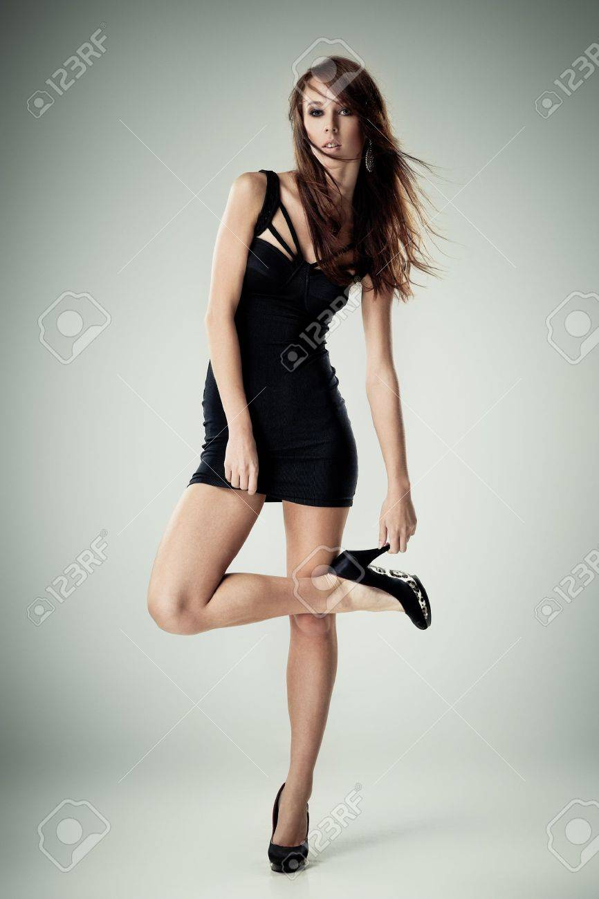 Young brunette lady in black dress posing on grey background Stock Photo - 10626455