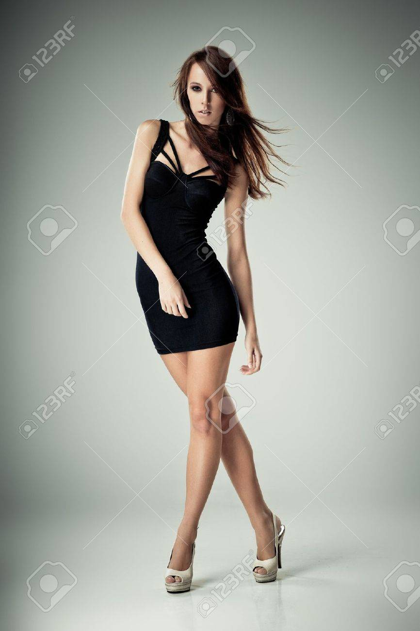 Young brunette lady in black dress posing on grey background Stock Photo - 10703317