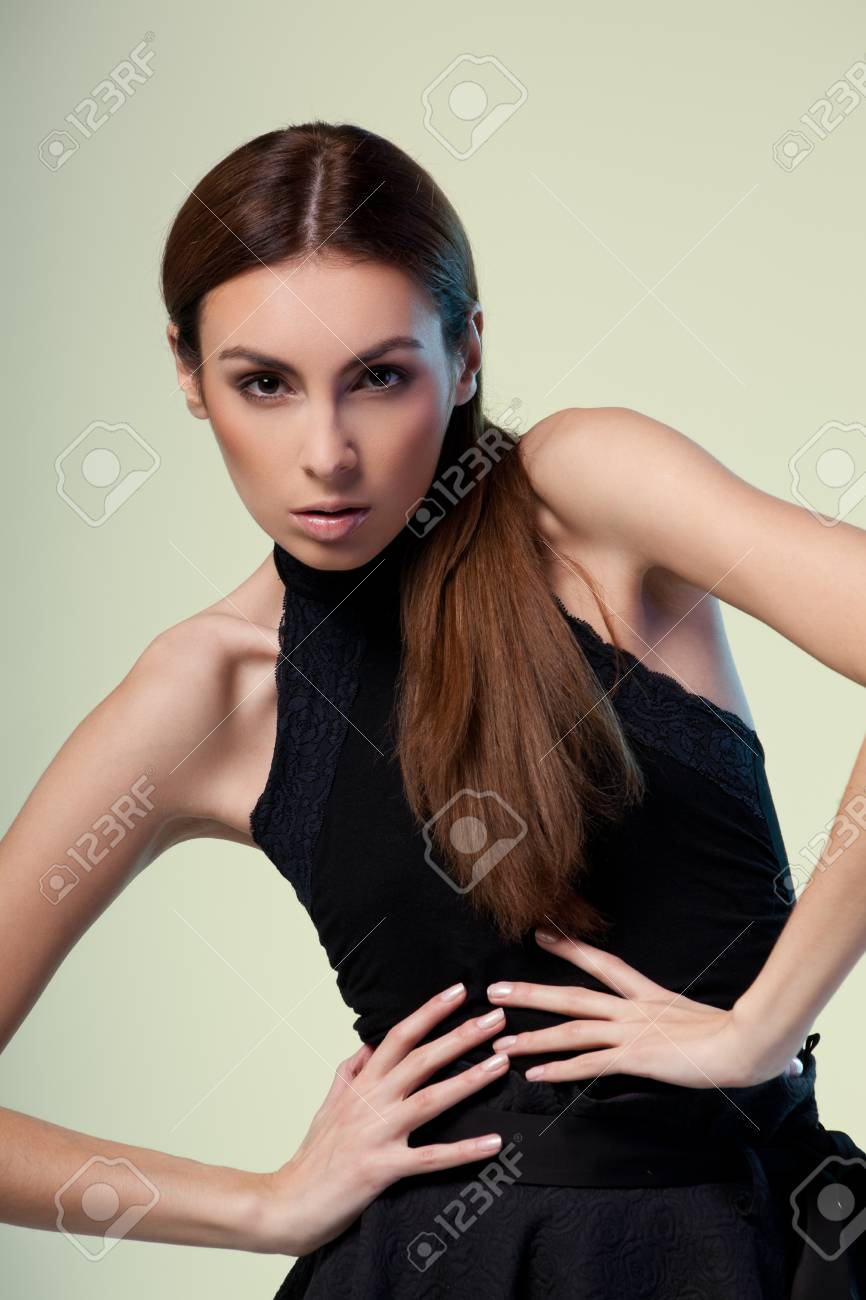 Young brunette lady in black dress posing on grey background Stock Photo - 12834474