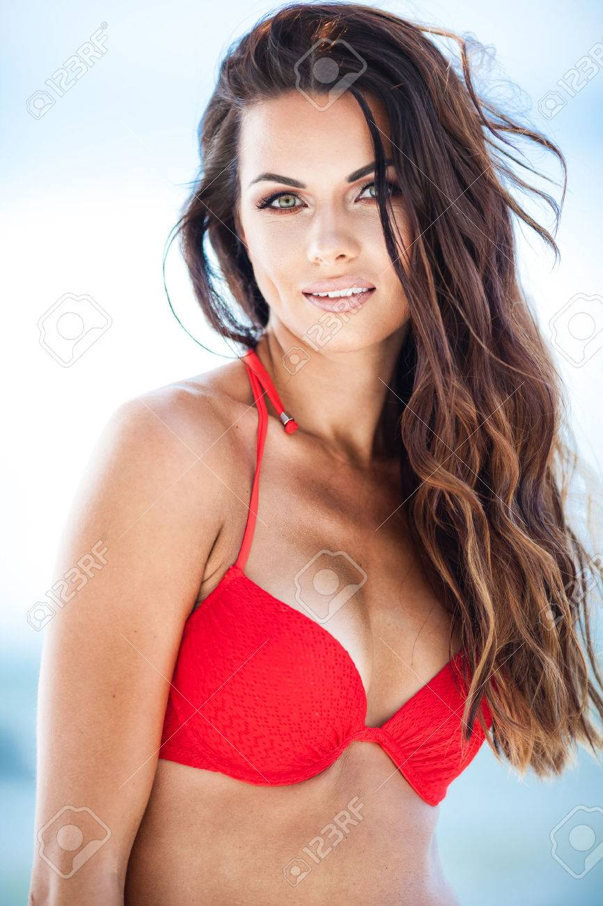 Sexy Brunette Girl In Red Swimsuit Posing On A Beach Stock Photo