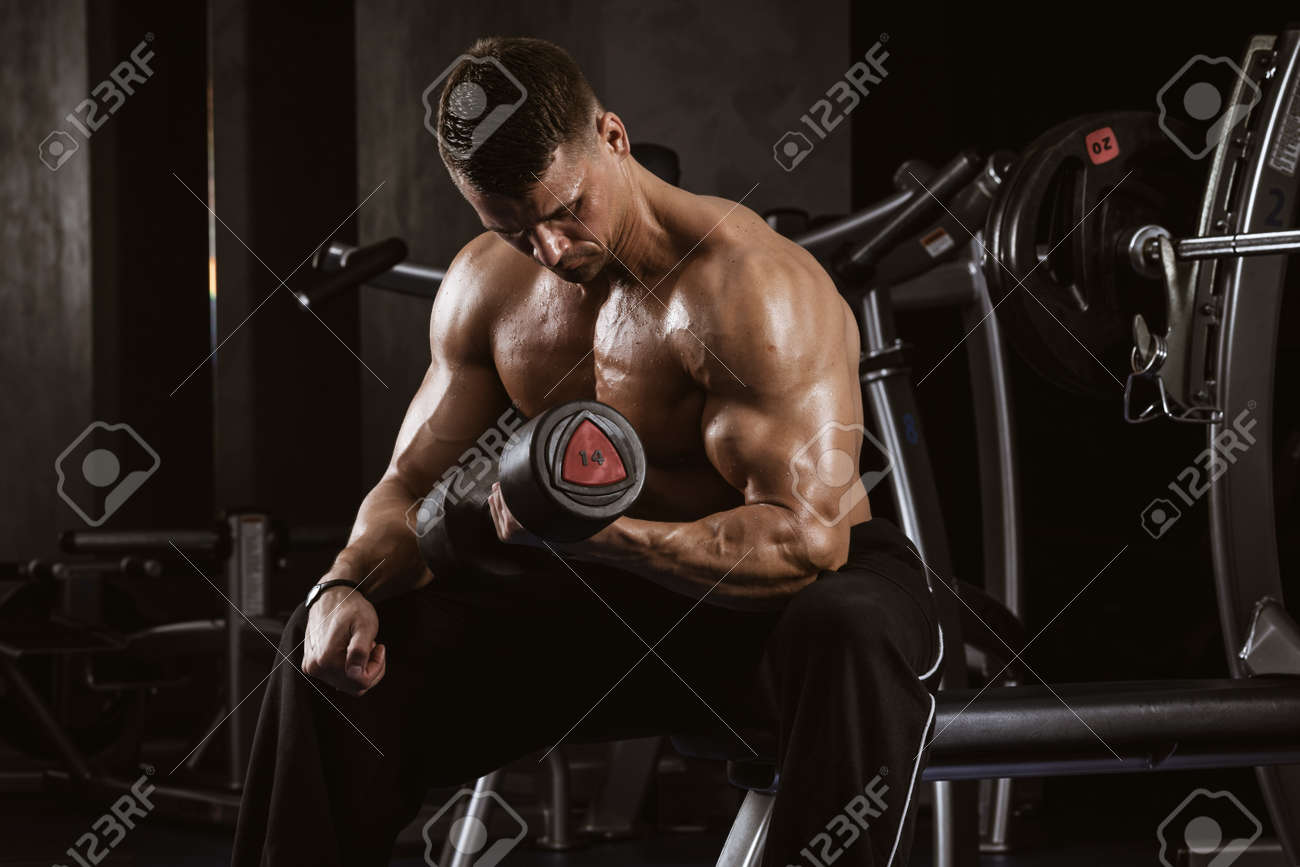 Fitness in gym, sport and healthy lifestyle concept. Handsome athletic man with torso making exercises. Bodybuilder male model training biceps muscles with dumbbell - 167170152