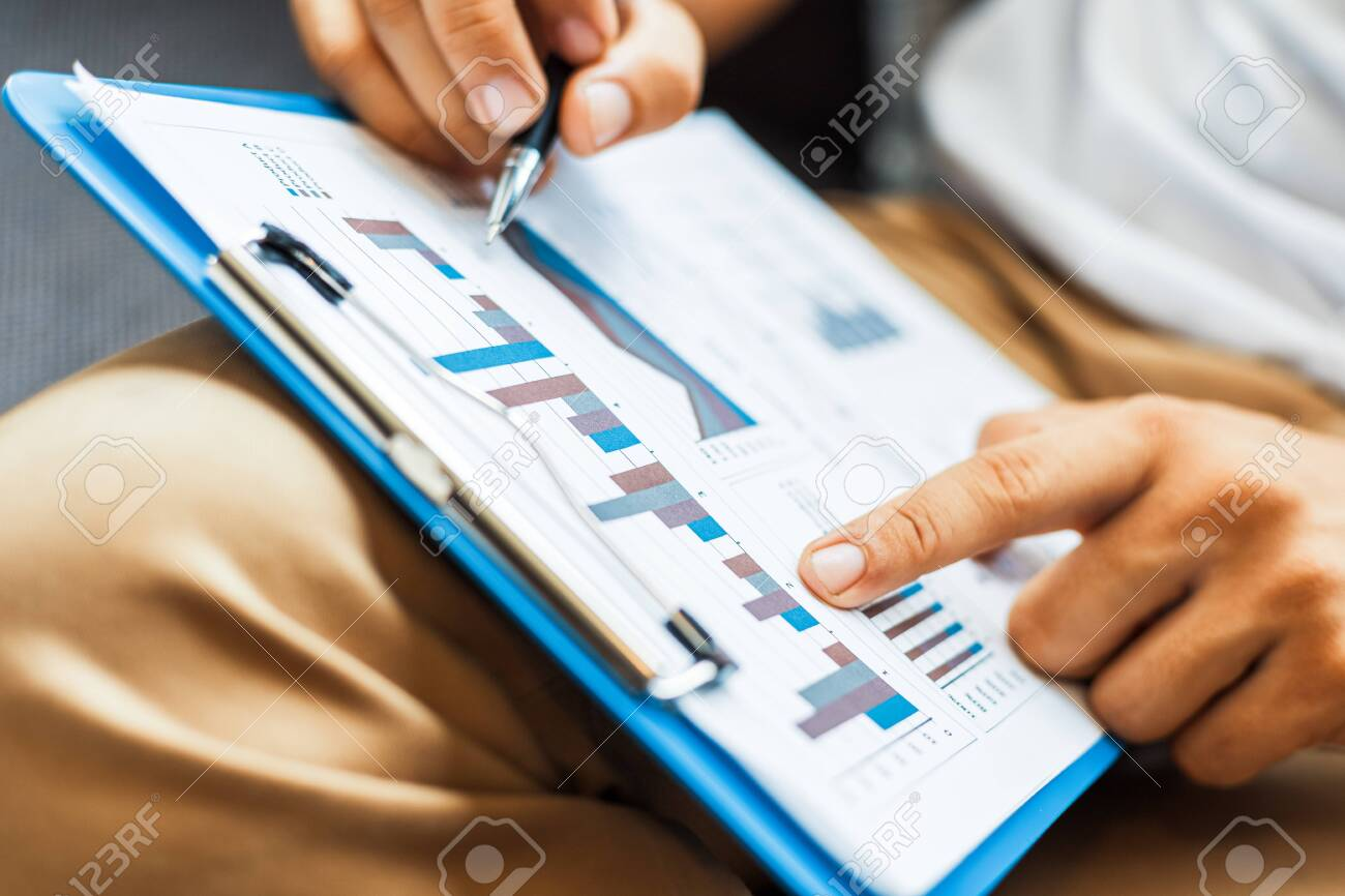 Businessman hold pen and working calculate data. document graph chart and report marketing. Business office concept. - 146274626