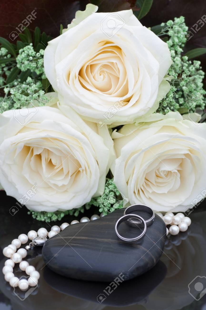 Les Anneaux De Mariage Présentés Dans Un Bouquet De Roses Blanches