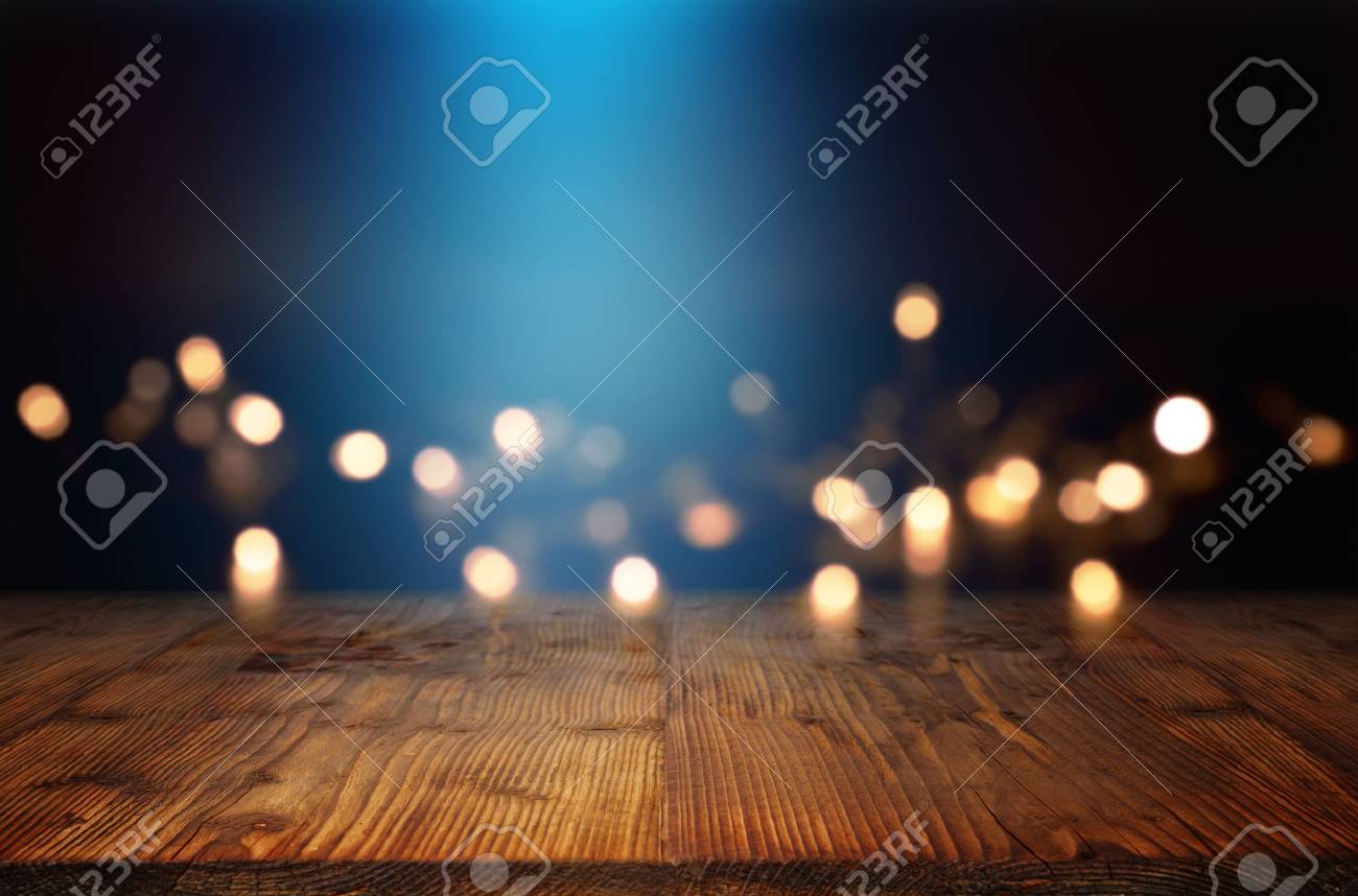 Bokeh background with blue light beam and an empty rustic wooden table for a festive christmas decoration - 84192558