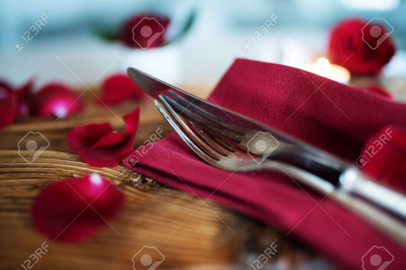 Romantic Table Setting In Red With Petals And Silver Cutlery