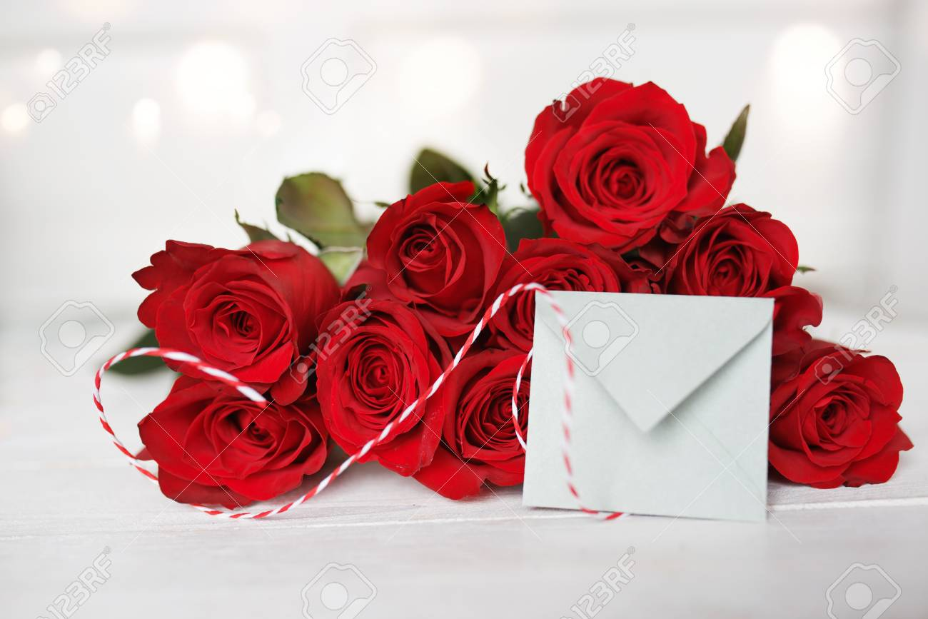 red roses with love letter on a white background with tender bokeh for valentines day stock