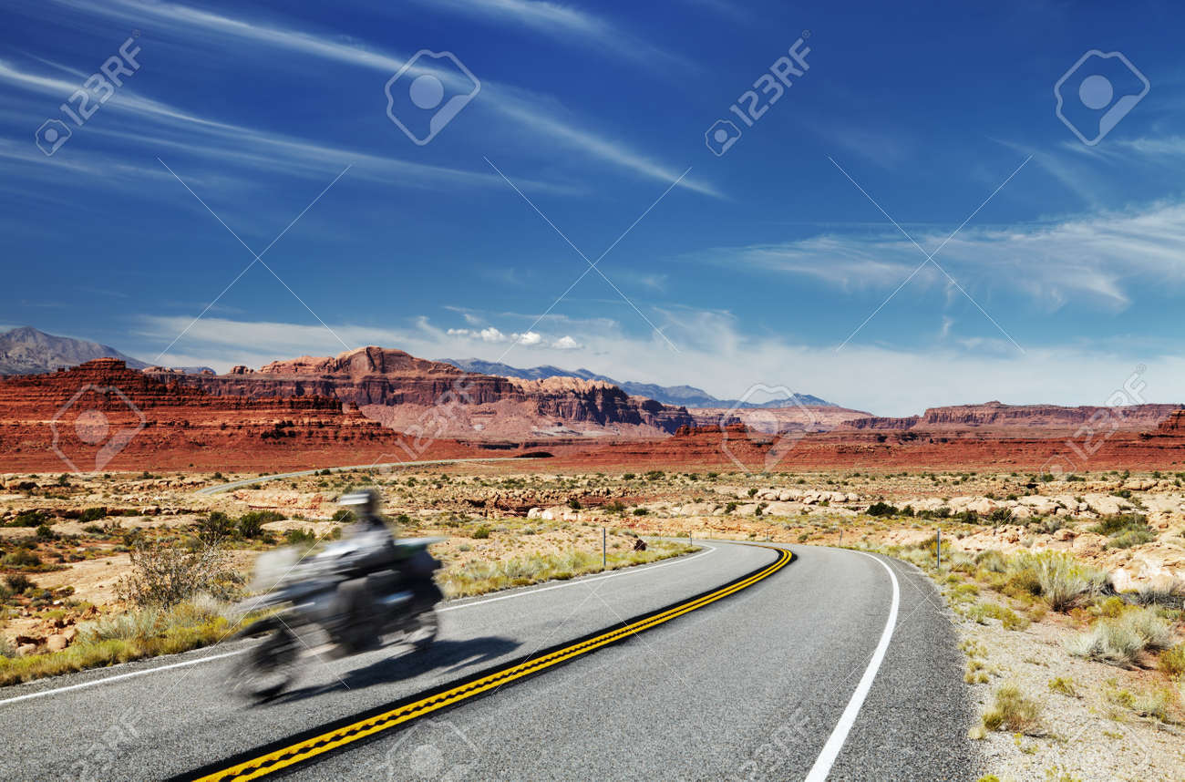 Motorcycle traveler riding in American highway, Glen Canyon, Utah, USA. Main object in motion blur - 165228560