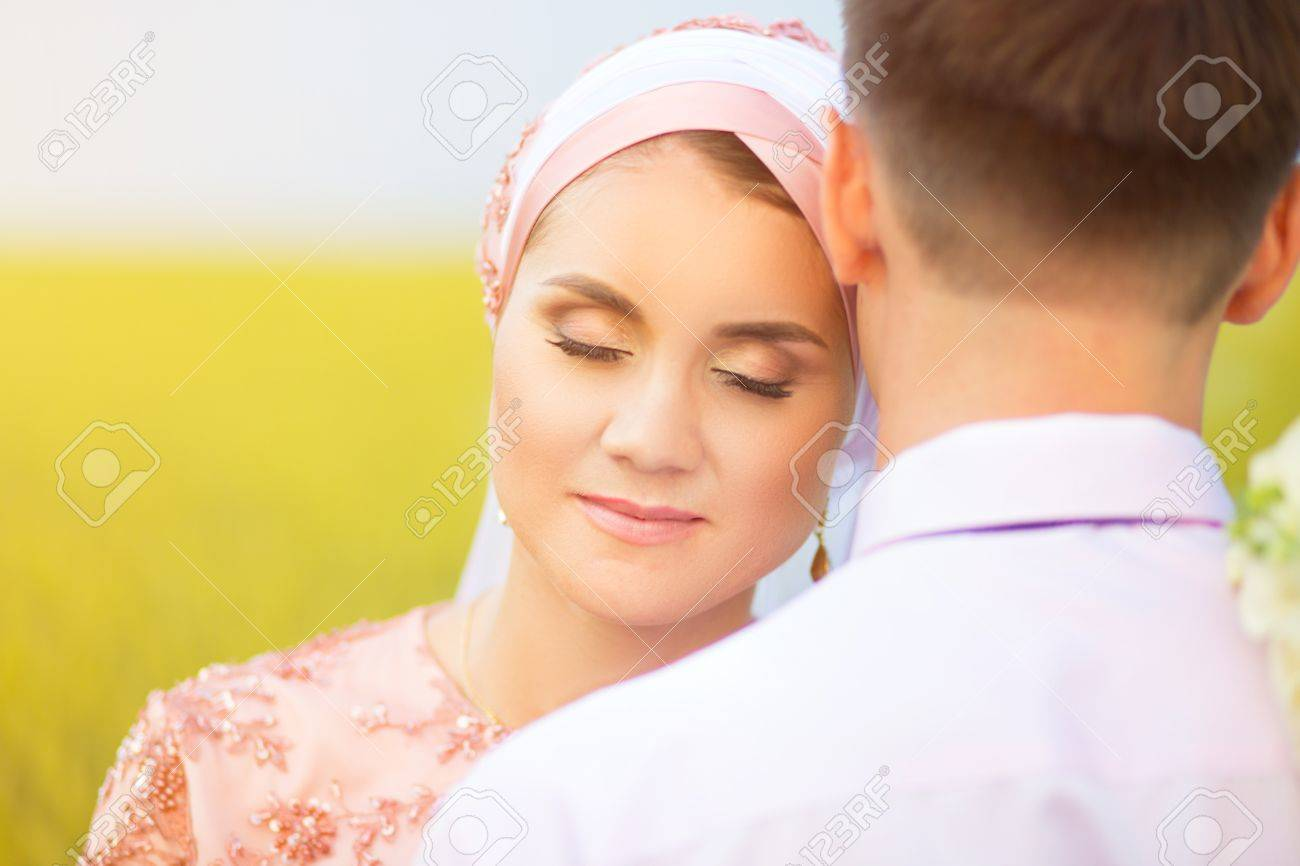 Beautiful couple just married on the field of wheat  Muslim marriage