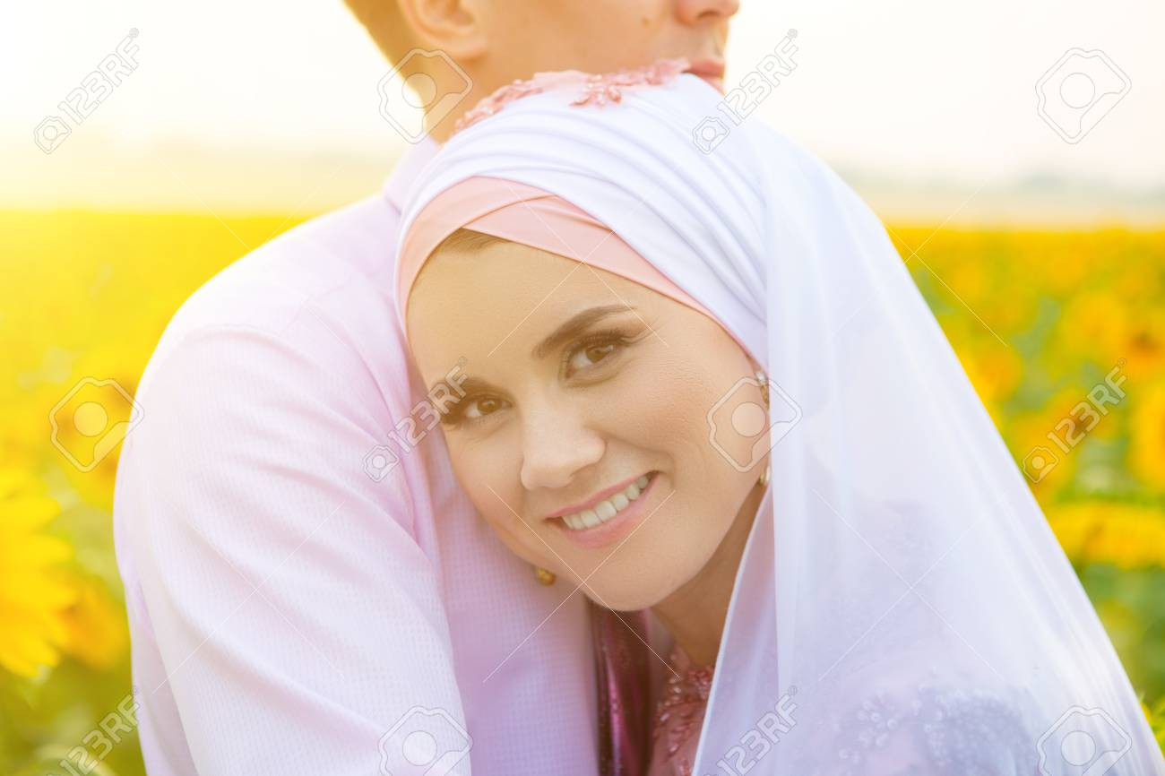 Smiling young islamic couple portrait on sunflowers field  Muslim