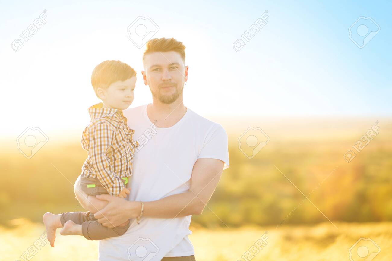 Happy father and son together having in the park on a warm sunny day. Family and love concept. - 120501723