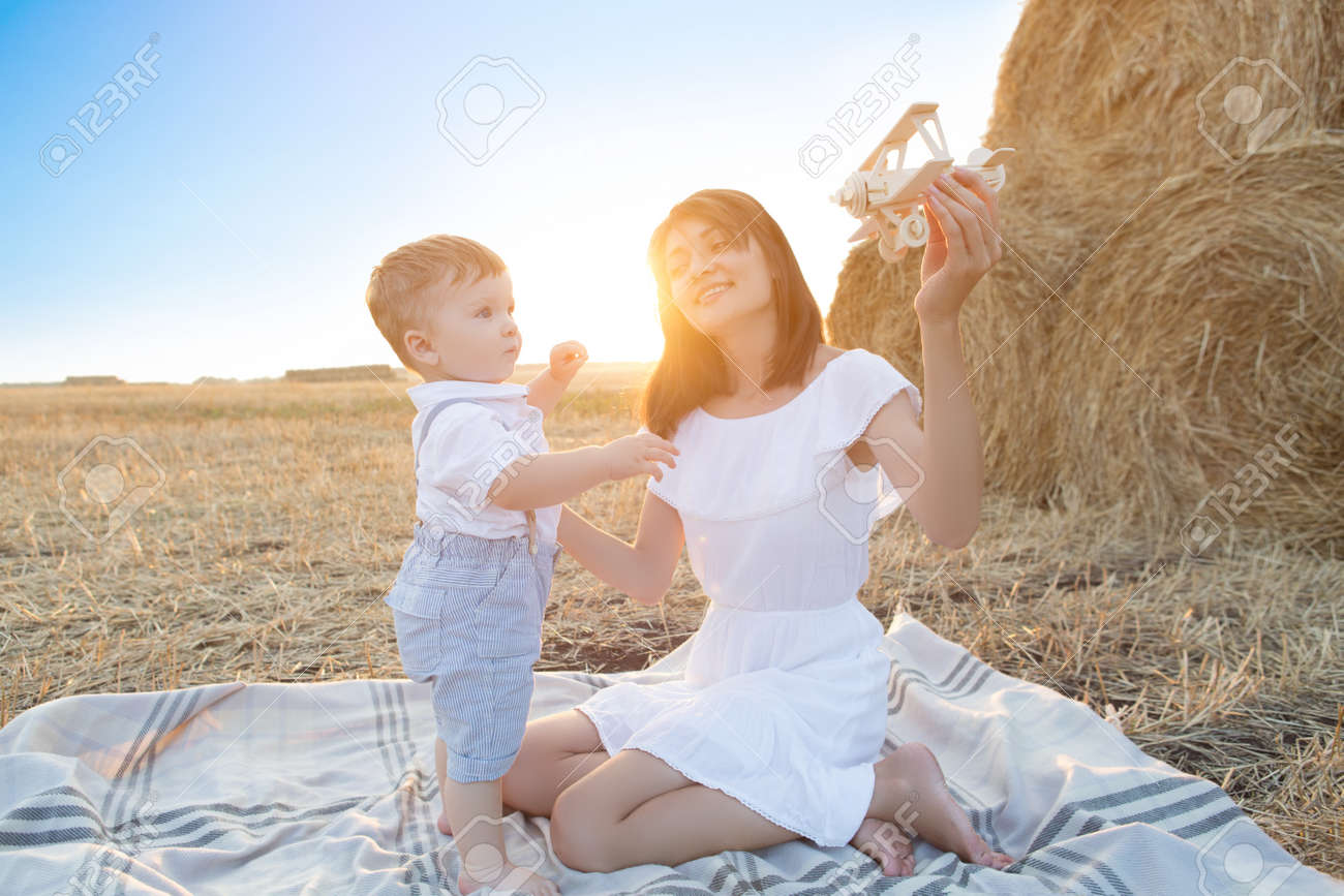 Woman and her son playing with toy airplane . - 149673250
