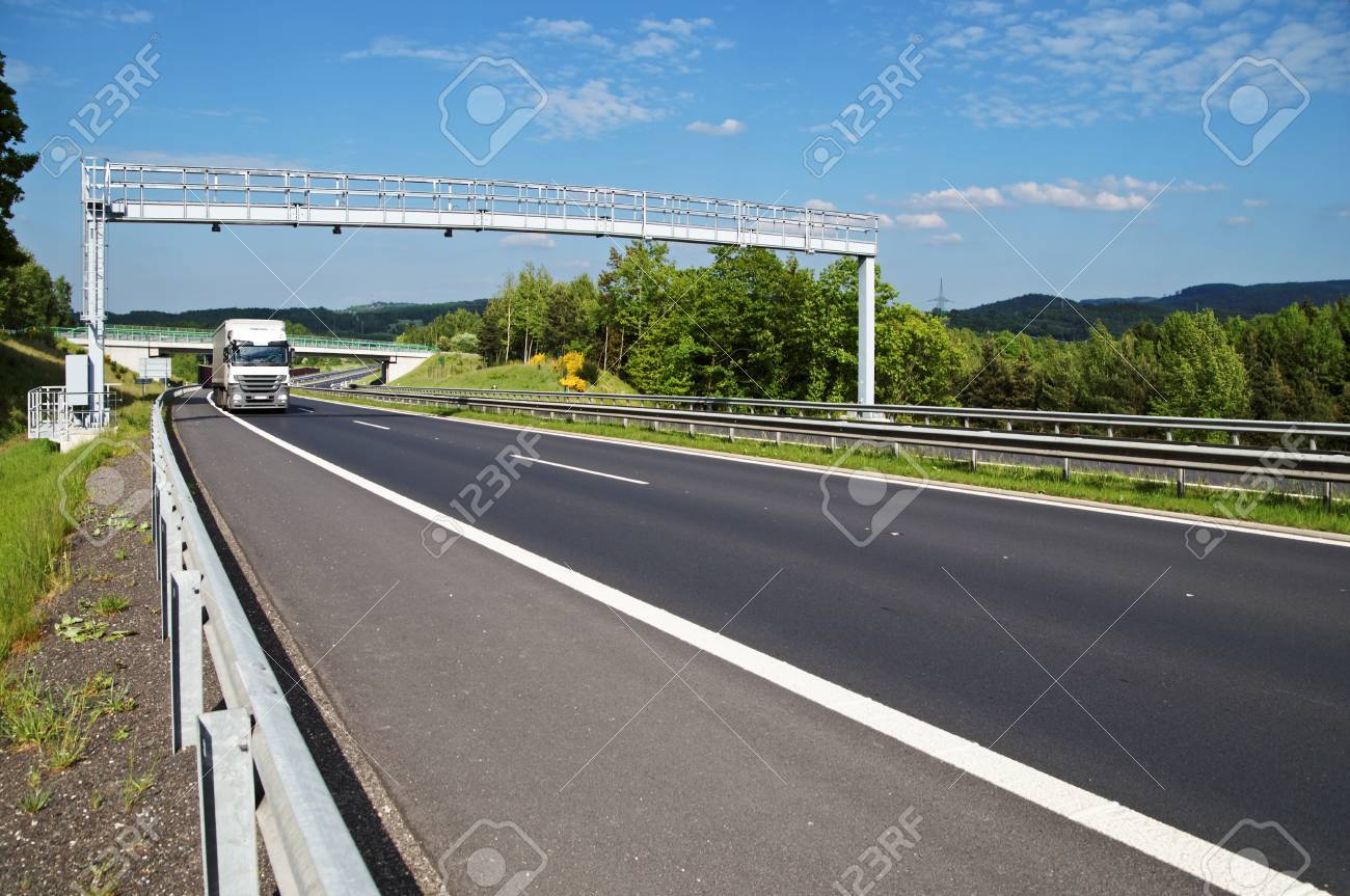 Highway electronic toll gates in wooded countryside  White truck