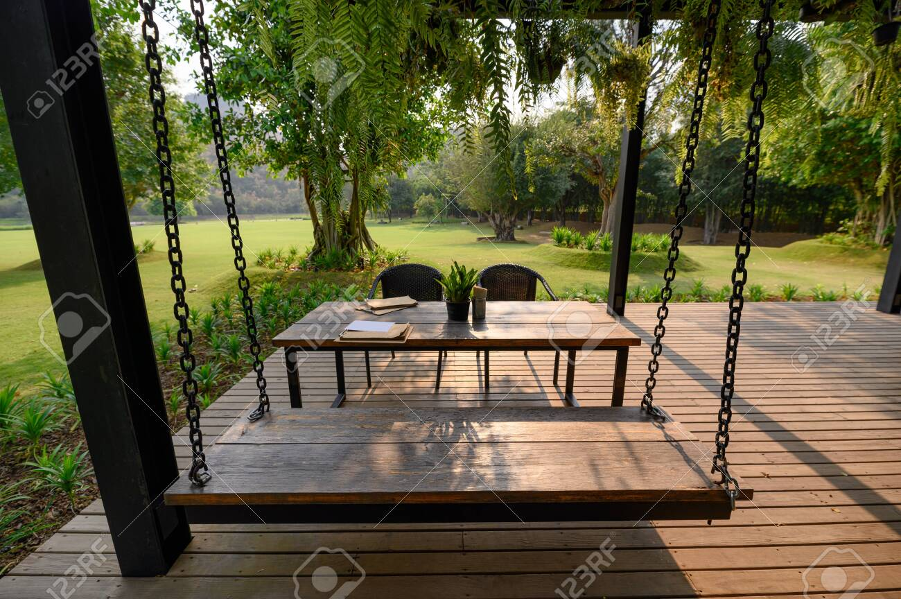photo wooden swing and chair in dining table with green flora on patio at sunset