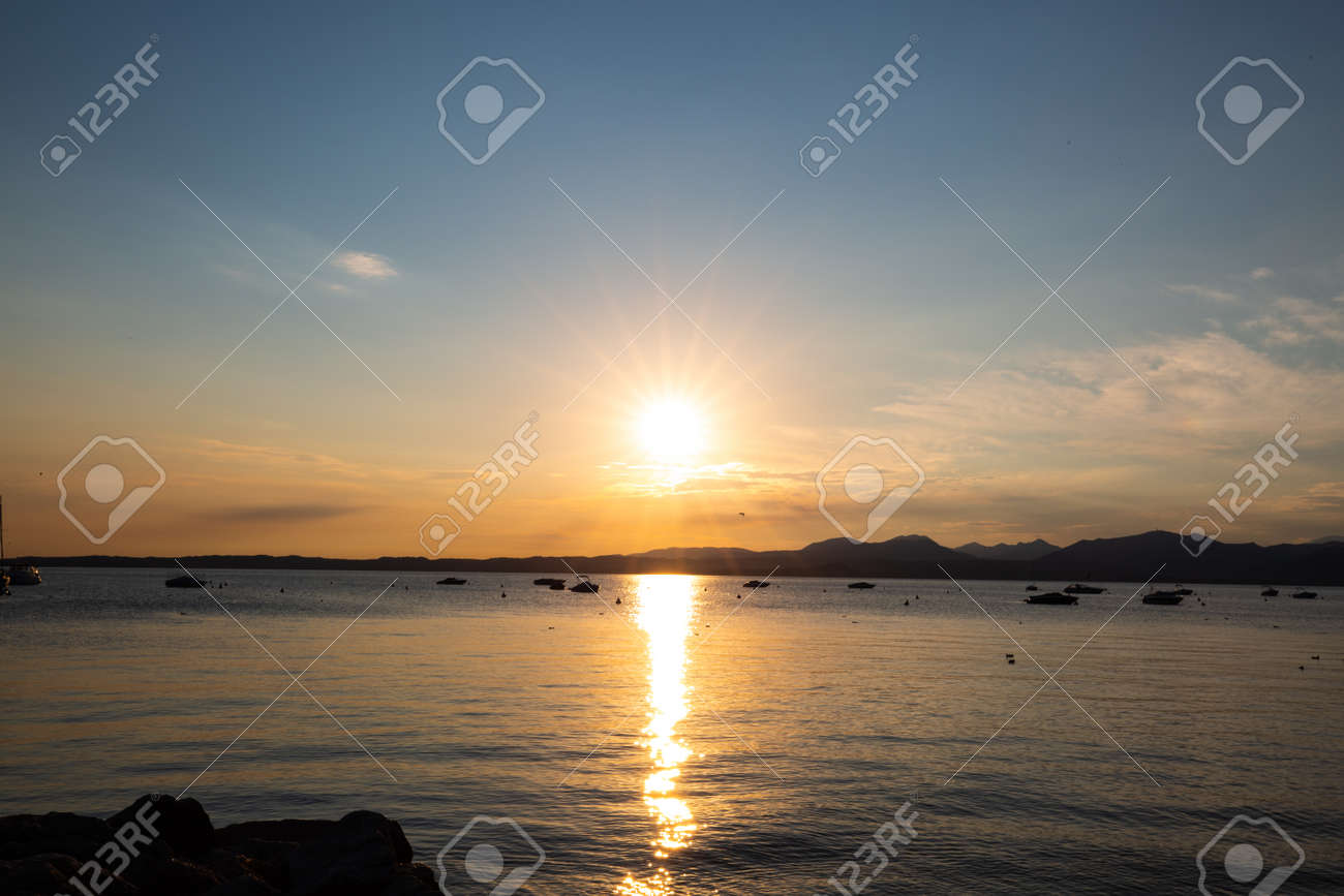 Sunset in Bardolino on Lake Garda with mountains in the background - 156183246