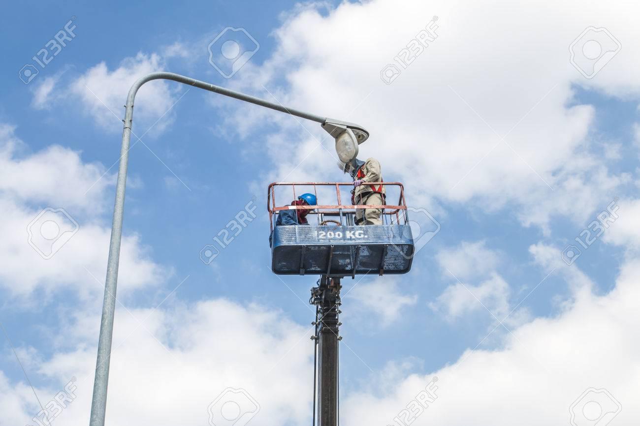 Electrical technician to repair street lightin by boom lift - 41947214