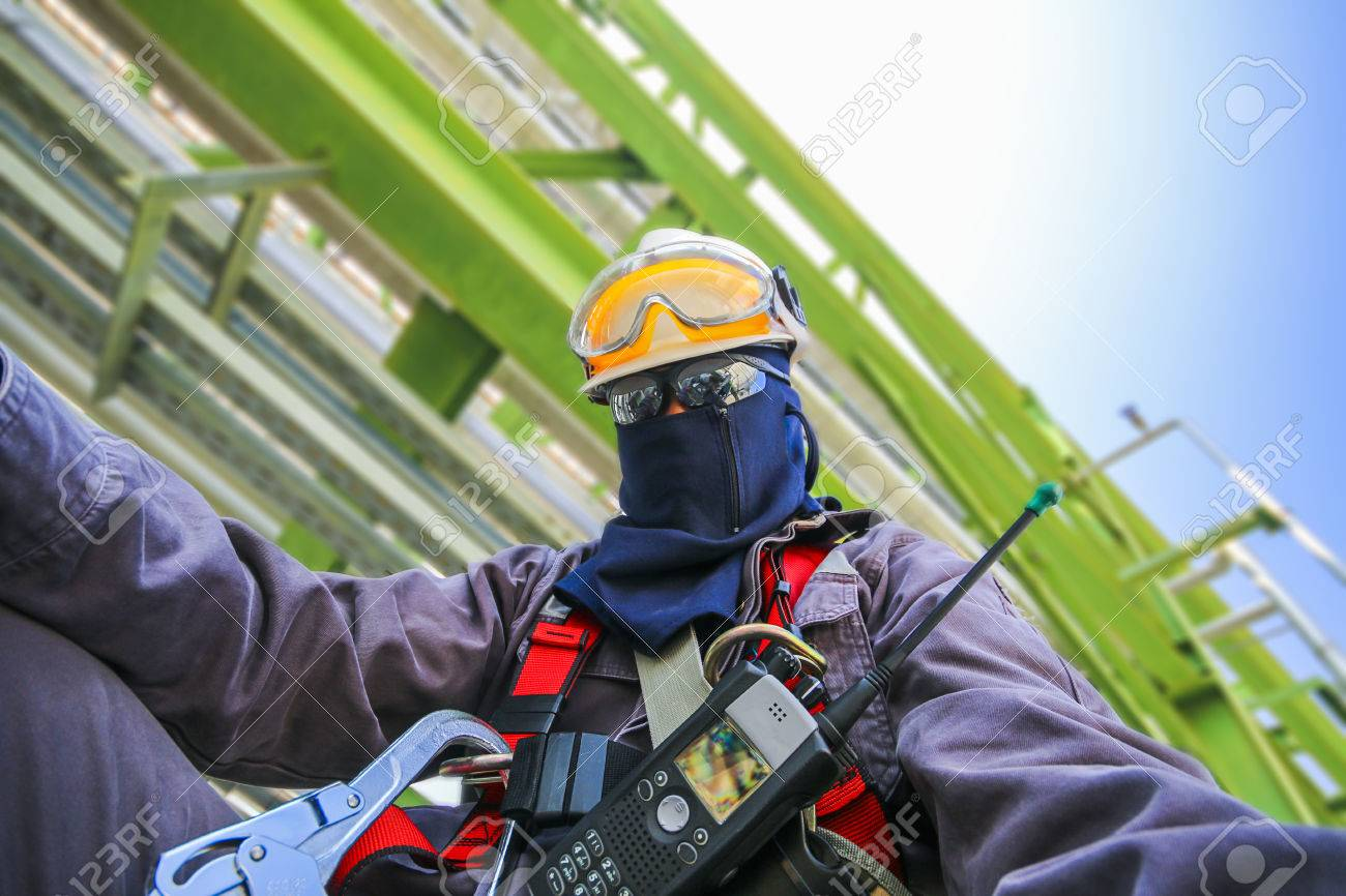 Man with safety personal protection equipment on structure in industrial plant background - 41948724