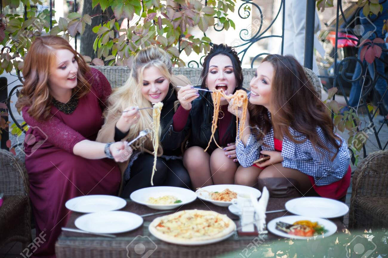 Four young women having lunch in a cafe. Pasta in a summer cafe. - 130224764