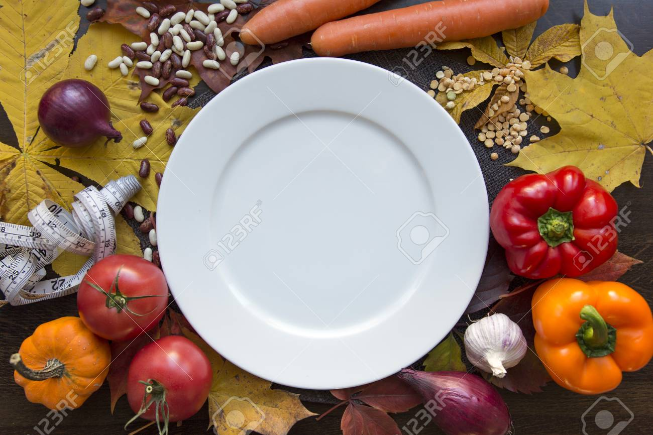 White emty plate with measuring tape and vegetables top view Stock Photo - 89216538