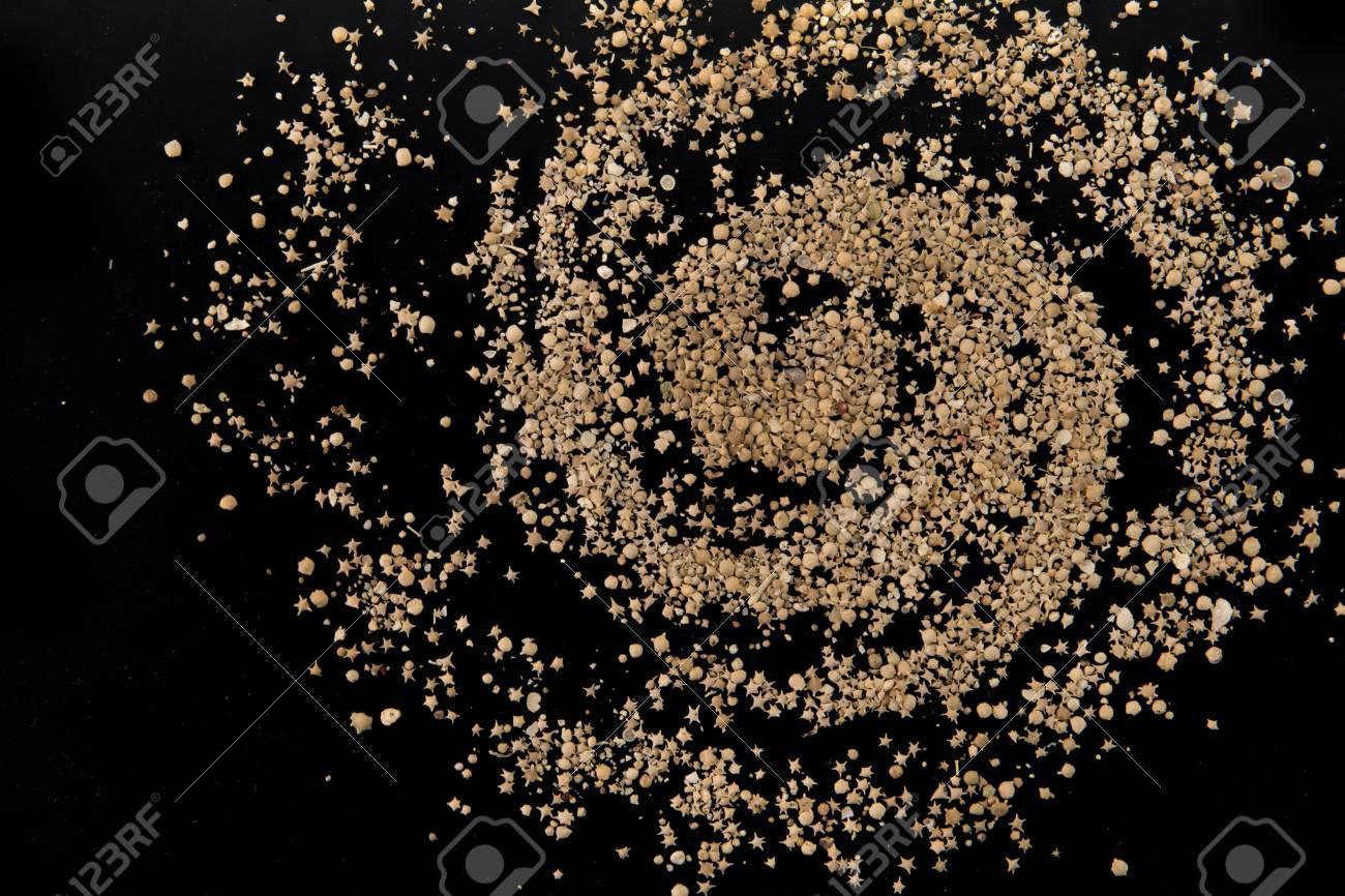Taketomi beach star sand closeup on black in a shape of Galaxy Stock Photo - 94815349
