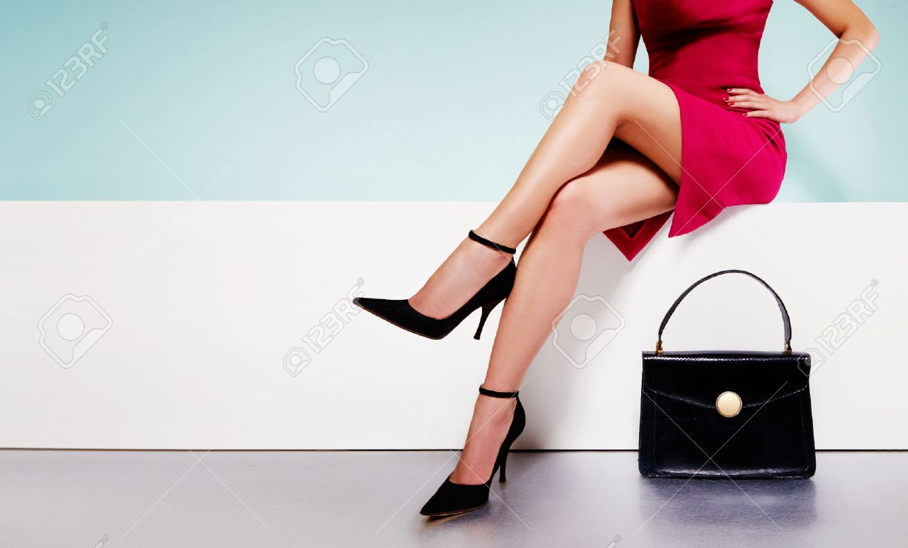 Beautiful legs woman wearing red dress with black purse hand bag with high heels shoes sitting on the white bench. with copyspace. - 61840863