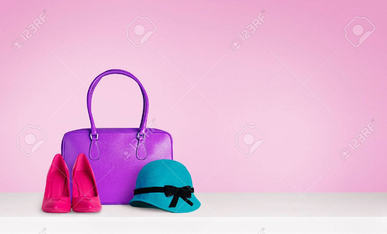 Colorful woman fashion accessories on the table isolated on pink. Red heels and a blue green hat and A purple leather bag. - 61840871