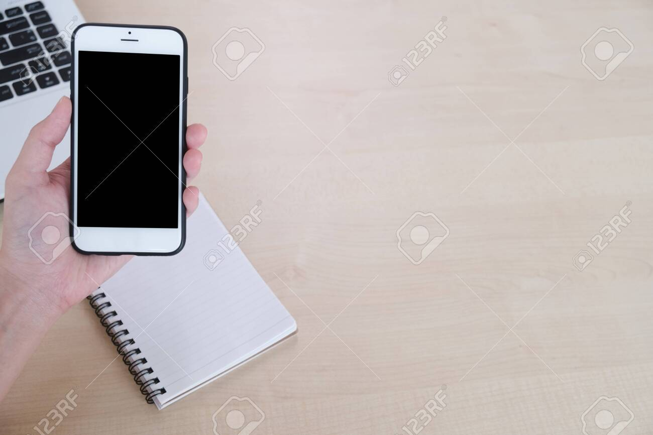 Top view of woman hand use cell phone on the table, empty book and laptop background, copy space, working and freelance concept - 122663064