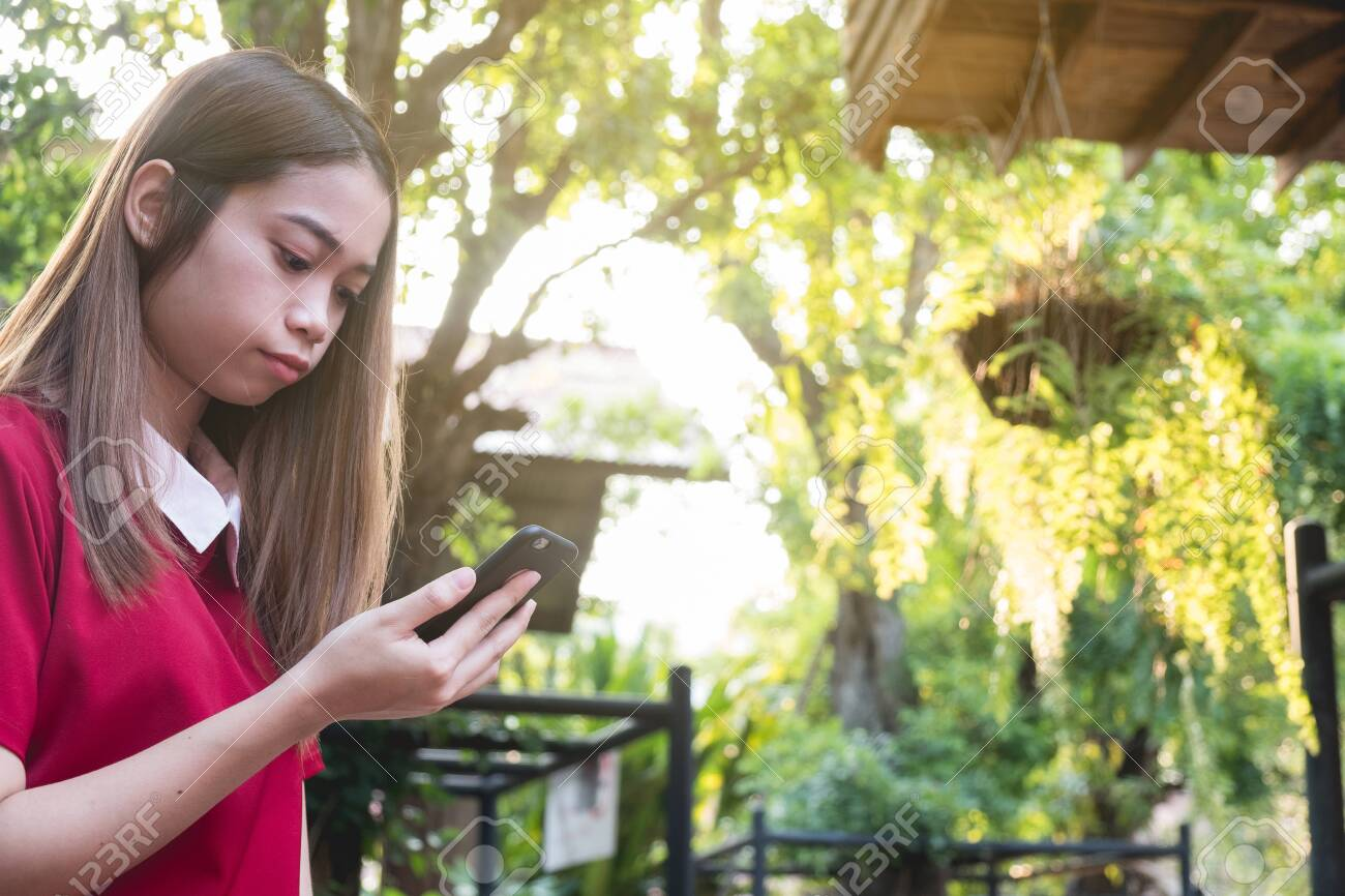 Woman using mobile phone while stand in the park - 122663200