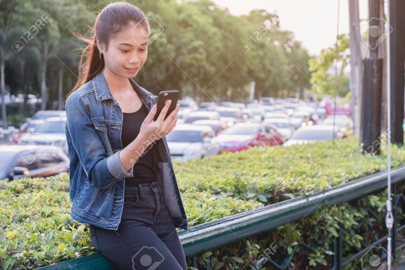 Woman using cell phone with traffic jam background, close up, portrait beautiful asia woman - 122663460