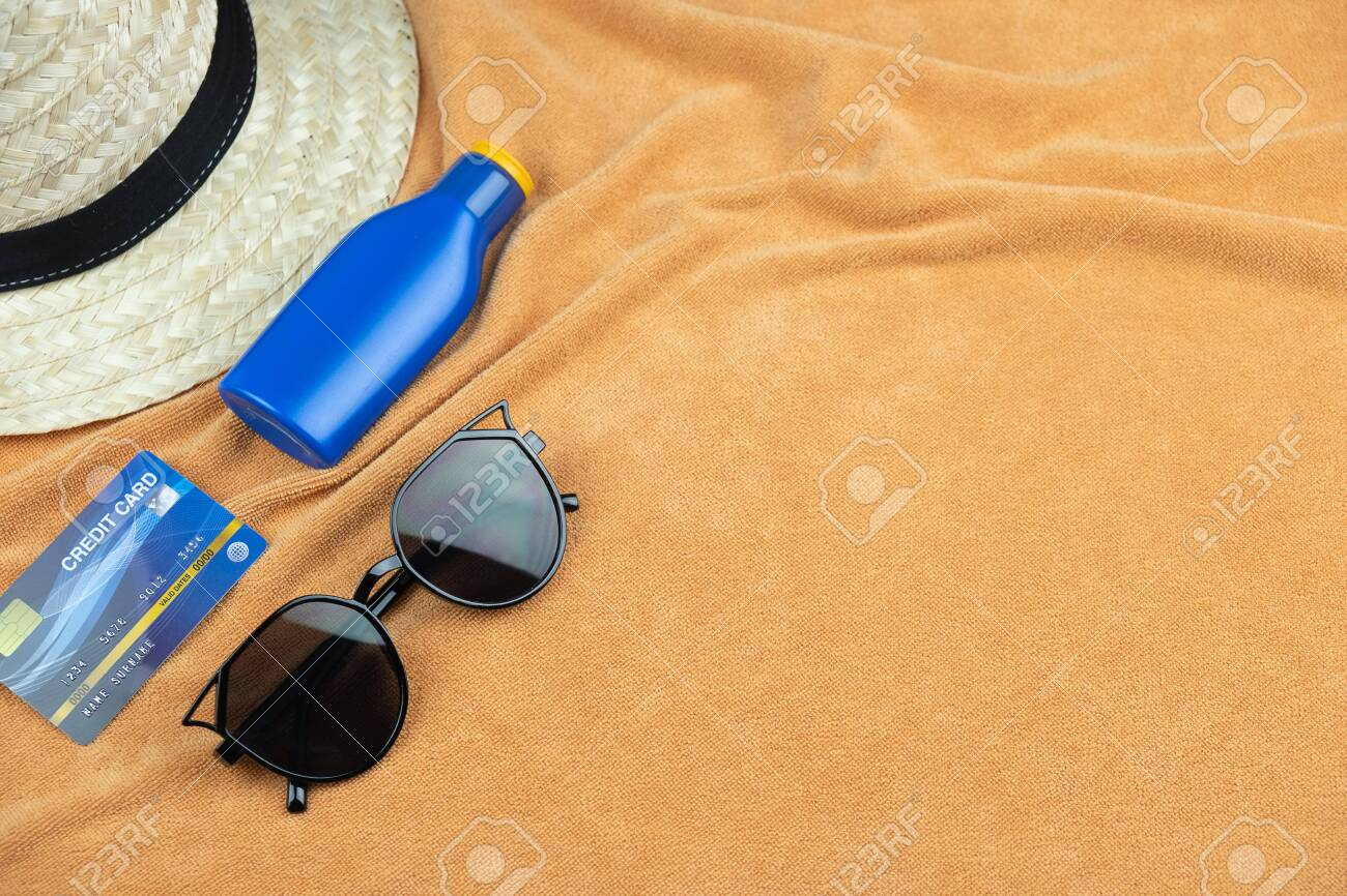 Top view of beach background. eyeglasses and credit card and sunscreen lotion and woven hats, trevel summer concept - 133765191