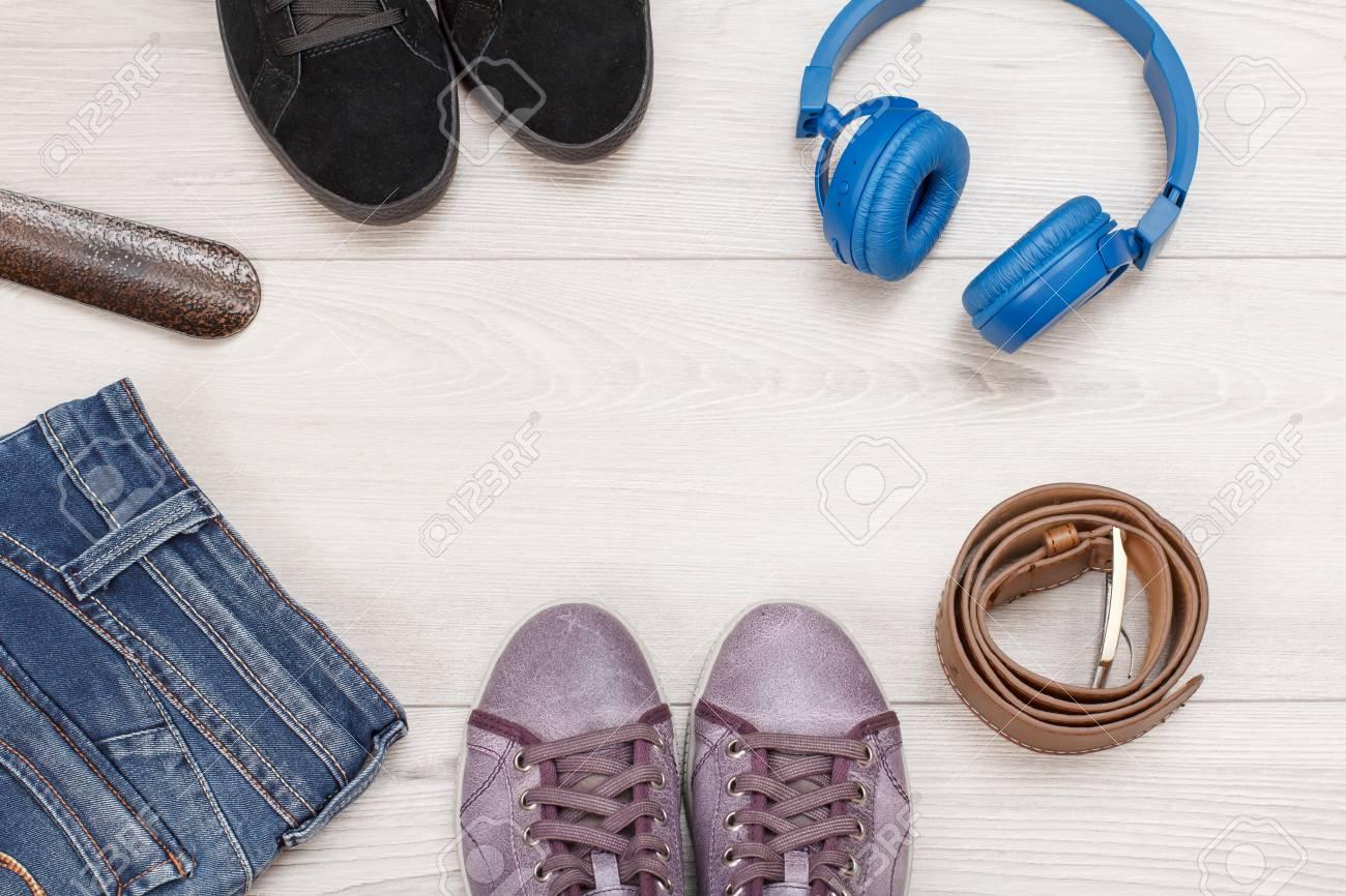 c06fe570 Foto de archivo - Ropa de mujer, calzado y accesorios. Zapatillas negras,  calzador, jeans, zapatillas de color rosa, cinturón de cuero y auriculares  sobre ...